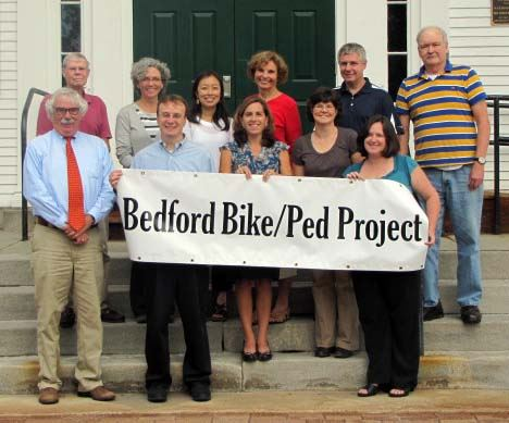 A group of people holding a Bedford Bike and Pedestrian Project banner
